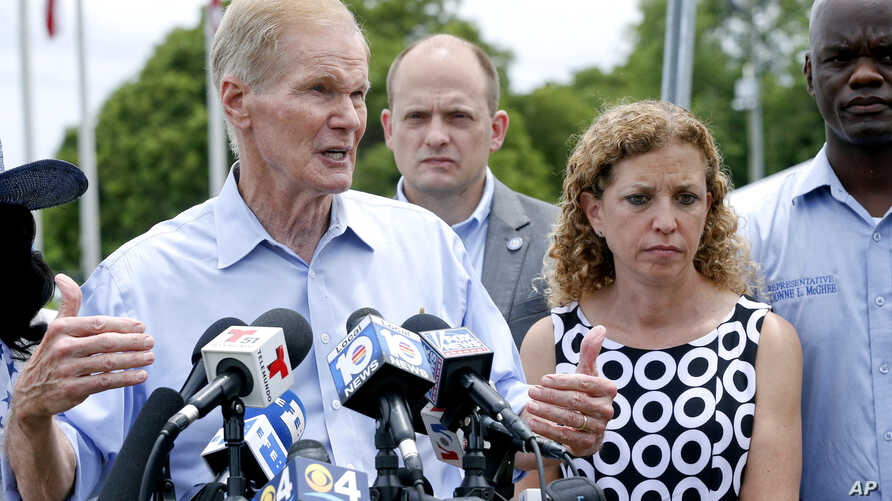 U.S. Sen. Bill Nelson, with U.S. Representative Debbie Wasserman Schultz, right, speaks during a news conference in front of the Homestead Temporary Shelter for Unaccompanied Children, June 23, 2018, in Homestead, Fla. Nelson and four of the state's
