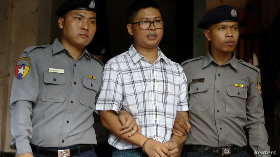 Detained Reuters journalist Wa Lone is escorted by police officers at Insein court in Yangon, Myanmar, July 16, 2018.