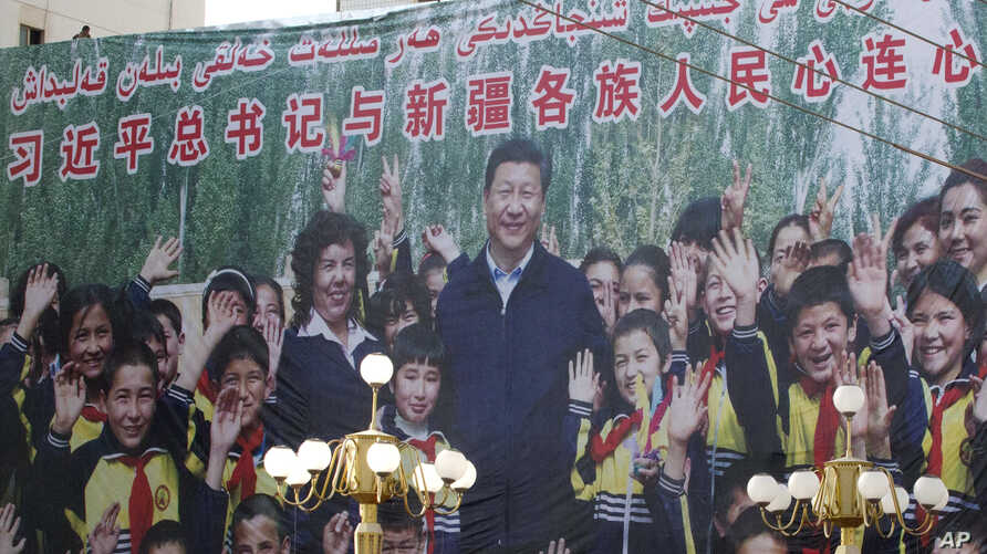 "FILE - A propaganda poster showing Chinese President Xi Jinping with ethnic minority children and the slogan which reads ""Party Secretary Xi Jinping and Xinjiang's multi ethnic residents united heart to heart"" decorates the side of a building in Kash"