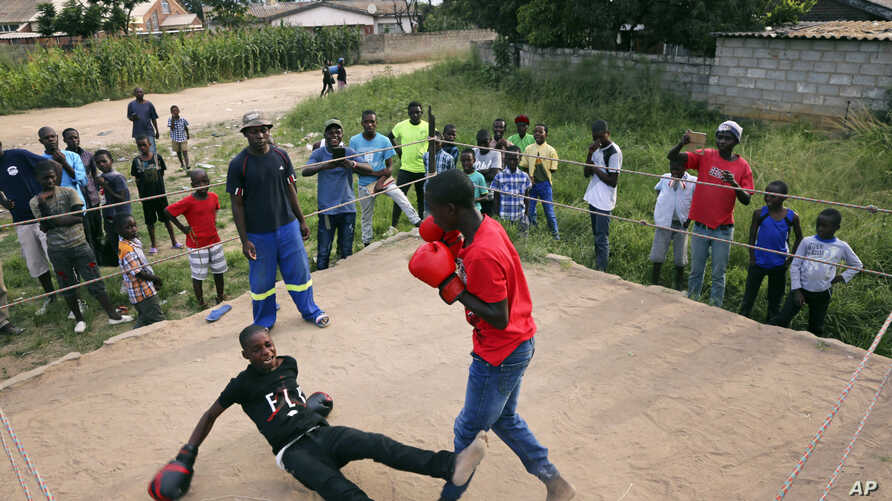 FILE - In this Feb. 12, 2017 photo, a young boy is knocked out during a boxing match in Chitungwiza, Zimbabwe.