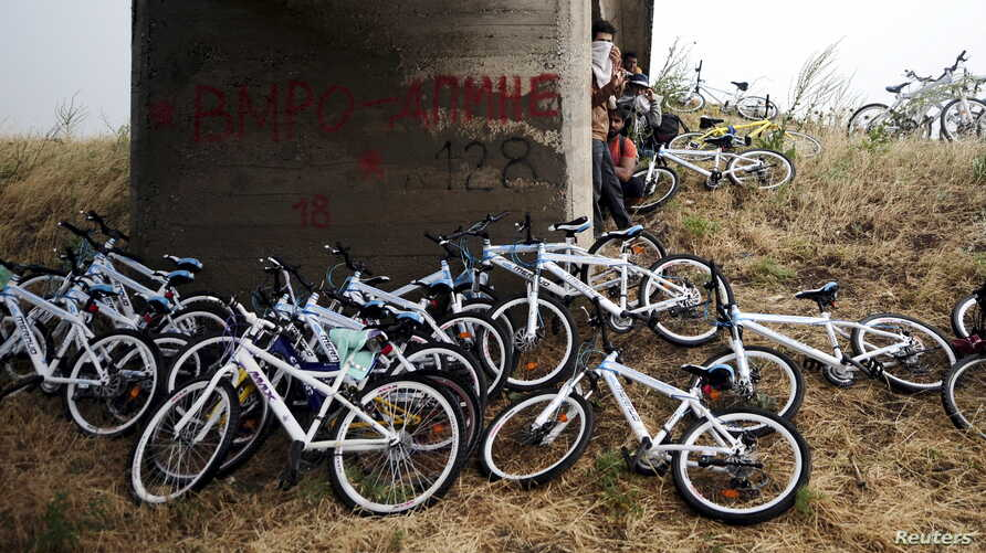 Immigrants from Syria stand near their bicycles as they hide from the rain under a bridge near the Greek border with Macedonia,  June 17, 2015. Hungary announced plans on Wednesday to build a four-metre-high fence along its border with Serbia to stem
