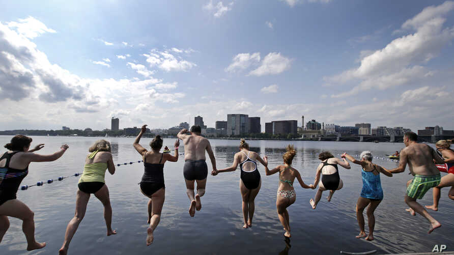 """People dive into the Charles River during the """"City Splash"""" event, July 18, 2017, in Boston."""