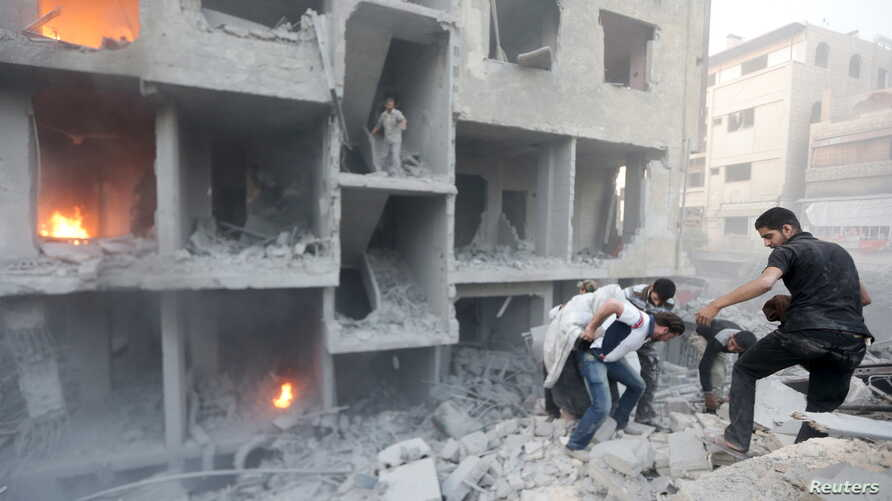 Men search for survivors at a site activists said was hit by heavy shelling by forces loyal to Syria's President Bashar al-Assad in the Douma neighborhood of Damascus June 16, 2015.