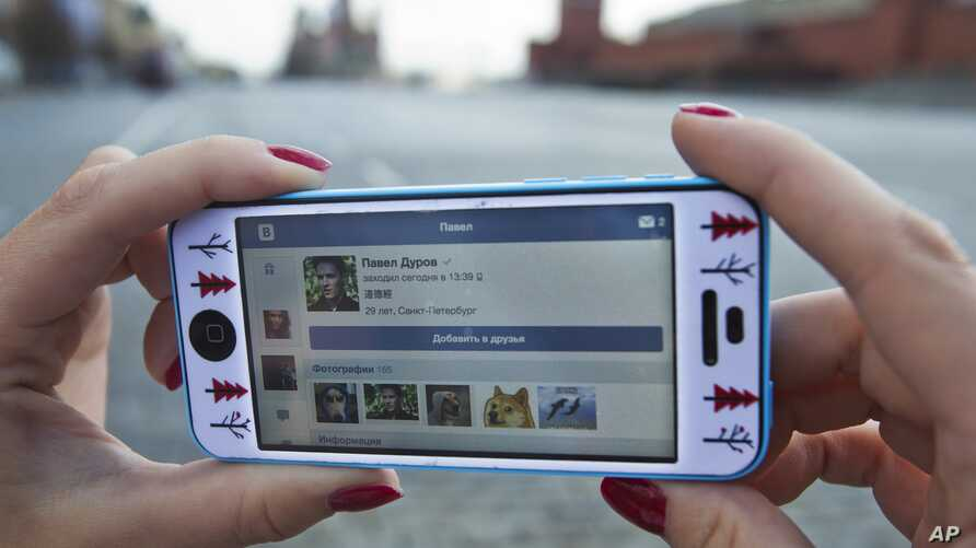 FILE - A user of Russia's leading social network internet site VKontakte, poses holding an iPhone showing the account page of Pavel Durov, the former CEO and founder of VKontakte, in Red Square in Moscow, Russia, Apr. 23, 2014. Mobile messaging ser...