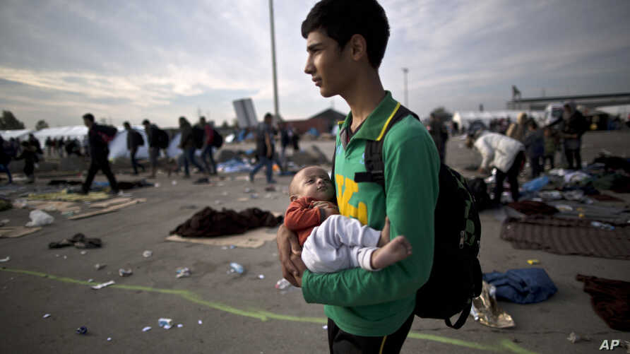 FILE -  Afghan refugee Rasoul Nazari, 15, holds his 10-month-old nephew Imran after crossing the border between Hungary and Austria in Nickelsdorf, Austria.