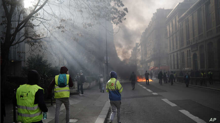 Yellow vest protesters walks towards a burning makeshift barricade during scuffles with riot police as they keep pressure on French President Emmanuel Macron's government, for the 13th straight weekend of demonstrations, in Paris, France, Saturday, F