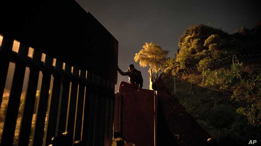 A Honduran migrant climbs the border wall separating Tijuana, Mexico and San Diego, before crossing to the U.S with his son in Tijuana, Mexico, Thursday, Nov. 29, 2018.