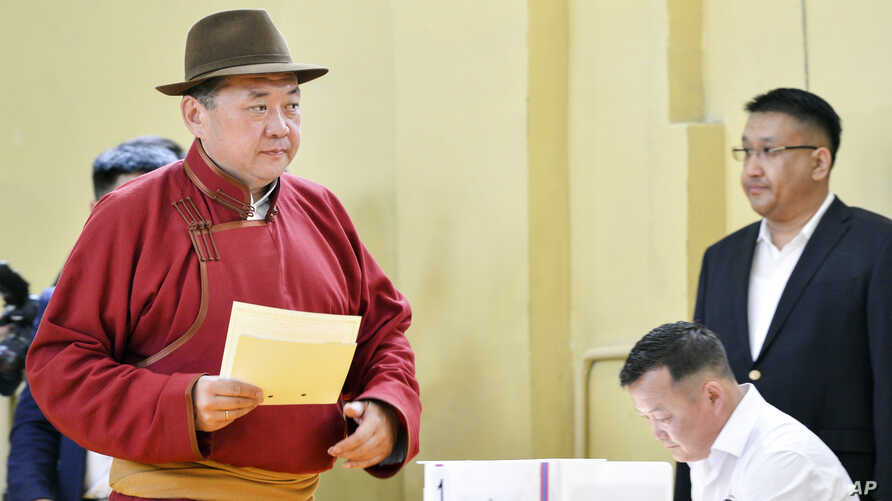 Speaker of Parliament and Mongolian People's Party presidential candidate Miyegombo Enkhbold, left, casts his vote at a polling station at a school in Ulaanbaatar, Mongolia, June 26, 2017.