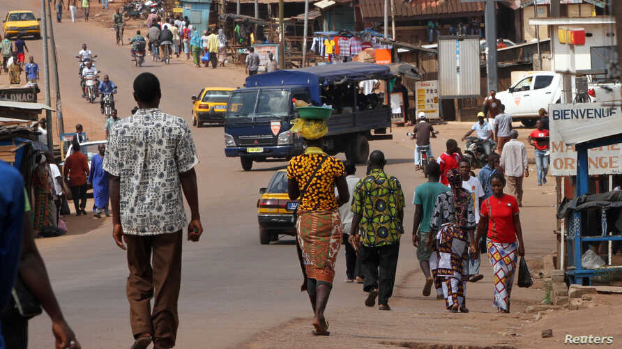 People walk as security forces travelling in a truck patrol a street in Gagnoa in western Ivory Coast, Dec. 2, 2010.