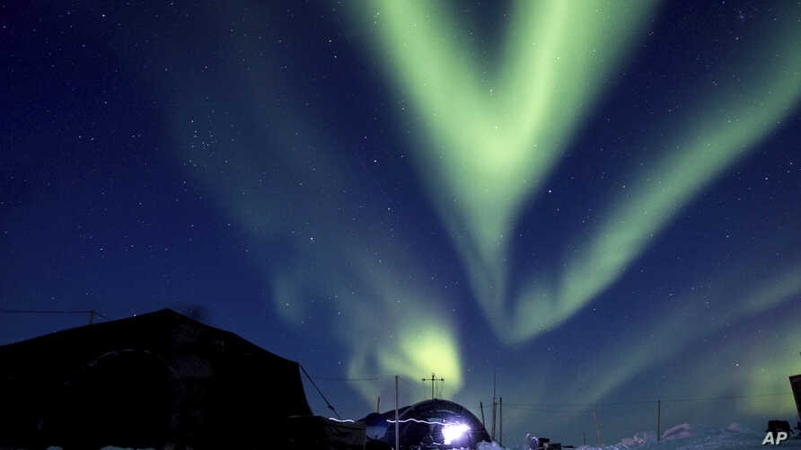 FILE - In this March 9, 2018, file photo provided by the U.S. Navy, the aurora borealis displays above Ice Camp Skate in the Beaufort Sea during Ice Exercise (ICEX) 2018. Scientists are seeing surprising melting in Earth's polar regions at times they