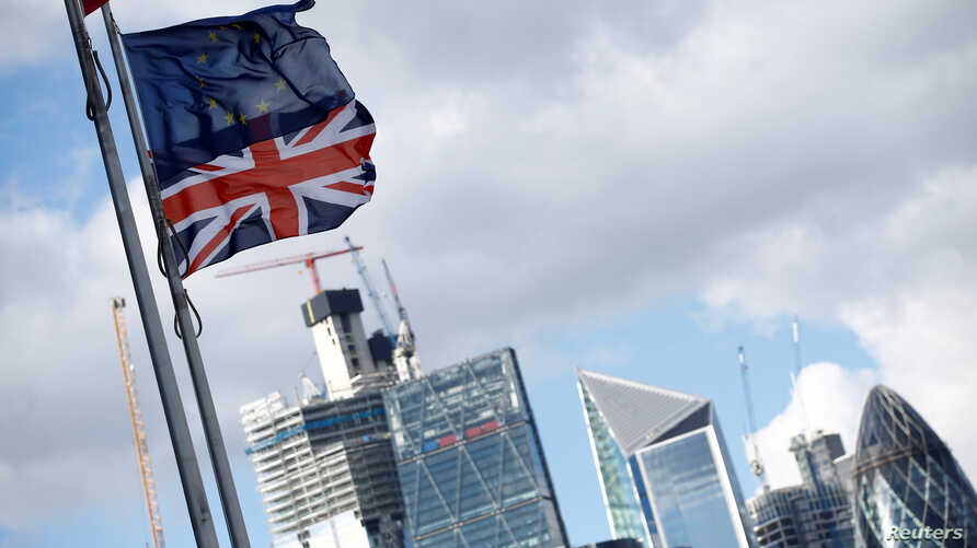 FILE - Flags flutter in the wind with the financial district in the background, in London, Sept. 23, 2018.