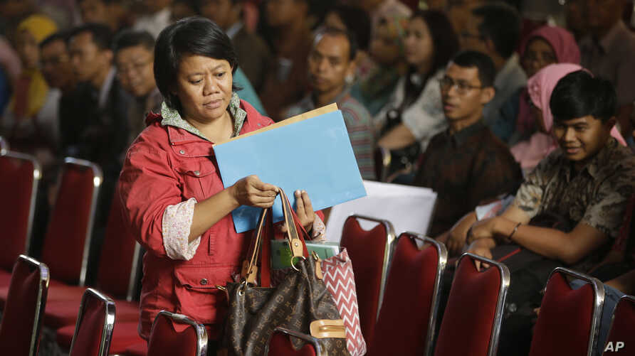 FILE - An Indonesian woman carrying documents registers her earnings for the government's tax amnesty at the tax office in Jakarta, Indonesia, in Jakarta, Indonesia, Sept. 29, 2016.