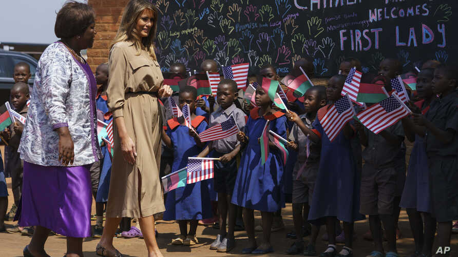 First lady Melania Trump is escorted by head teacher Maureen Masi as she arrives for a visits Chipala Primary School, in Lilongwe, Malawi, Oct. 4, 2018.