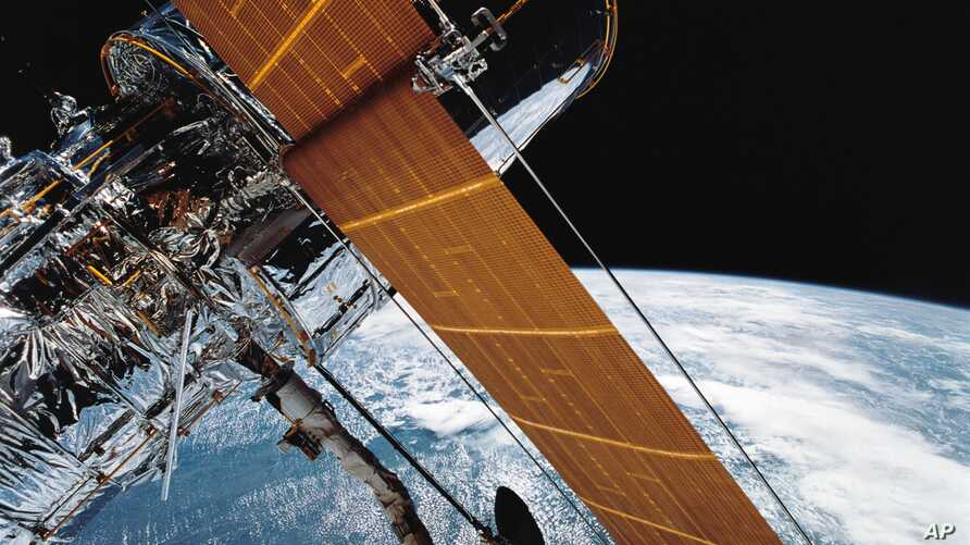 FILE - In this photograph provided by NASA, most of the giant Hubble Space Telescope can be seen as it is suspended in space by the shuttle Discovery's Remote Manipulator System following the deployment of part of its solar panels and antennae, April