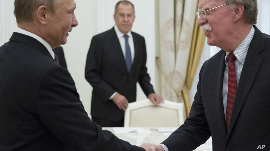 In this June 27, 2018 photo, Russian President Vladimir Putin, left, and U.S. National security adviser John Bolton greet each other as Russian Foreign Minister Sergey Lavrov looks on during their meeting in the Kremlin in Moscow.