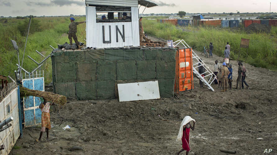 Displaced South Sudanese next to United Nations peacekeepers from Mongolia guarding the gate, at a makeshift camp at the United Nations Mission in South Sudan (UNMISS) base in the town of Bentiu, South Sudan, Sept. 22, 2014.