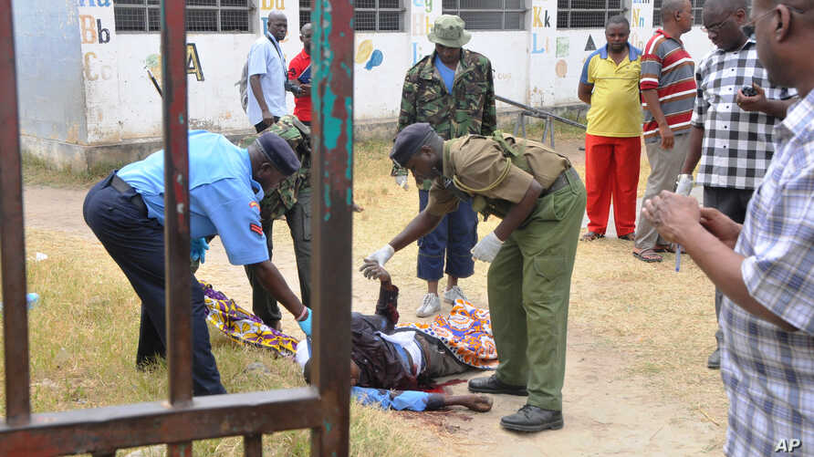Security officers examine the body of a pastor George Karidhimba Muriki of the Maximum Revival Center after he was shot dead by armed gunmen in Mombasa, Kenya, Jan. 11, 2015.