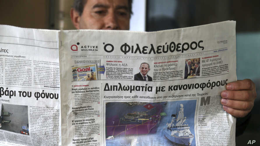 A man reads a Cypriot newspaper with a  front page carrying  a photo montage about Turkey's actions over Cyprus and international companies exploration for gas in the eastern Mediterranean  in capital Nicosia, Cyprus, Tuesday, Feb. 13, 2018.