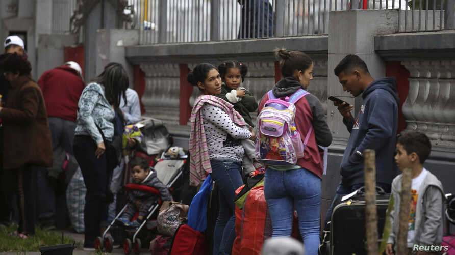 FILE - Venezuelan migrants wait on the grounds of their country's embassy for a bus that will transport them to the airport, in Lima, Peru, Sept. 8, 2018.