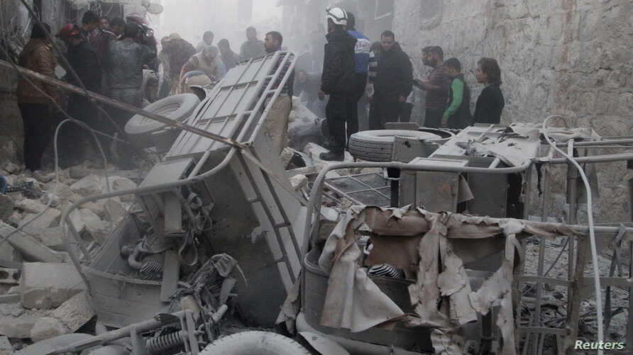 Men inspect a site hit by what activists said was a barrel bomb dropped by forces loyal to Syria's President Bashar al-Assad on al-Marjeh neighborhood of Aleppo, Nov. 12, 2014.