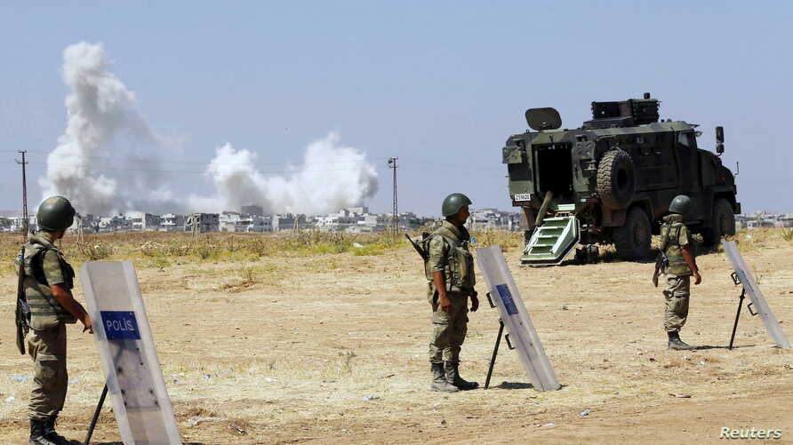 Turkish soldiers stand guard near the Mursitpinar border gate in Sanliurfa province as smoke rises in the Syrian town of Kobani in the background, June 27, 2015.