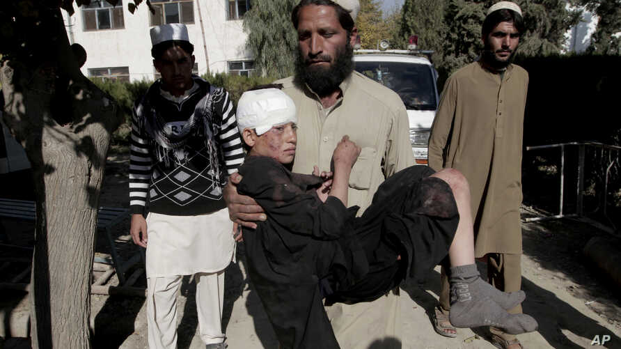 FILE - An Afghan man carries an injured boy to a hospital after two roadside bombs struck the Achin district of Jalalabad, east of Kabul, Afghanistan, Nov. 28, 2013.