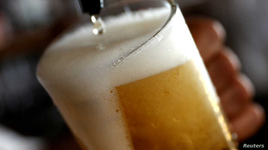 FILE - A pint of beer is poured into a glass in a bar in London, Britain, June 27, 2018.