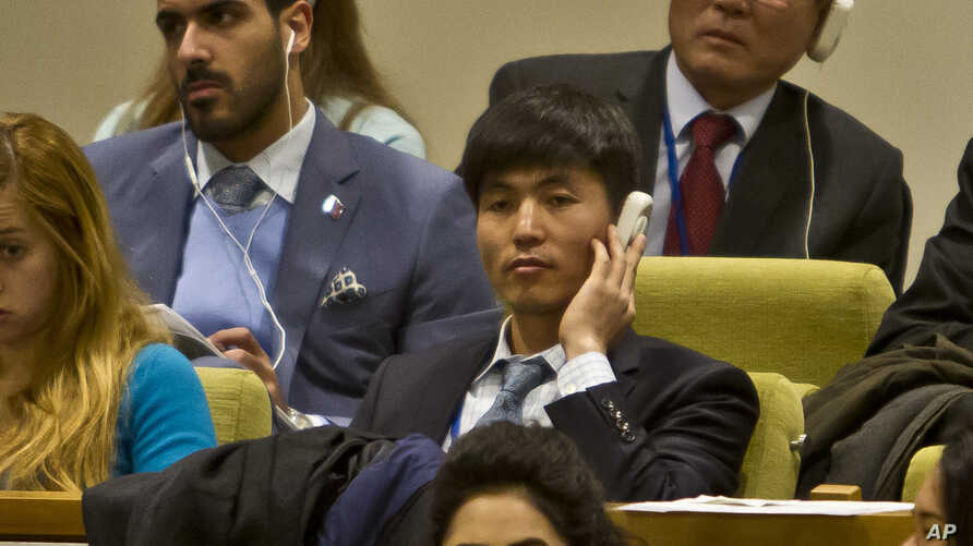 FILE - North Korean dissident Shin Dong-Hyuk, center, holds his earpiece as he listens during a meeting of the U.N. General Assembly human rights committee on a proposal to refer North Korea to the International Criminal Court for alleged crimes agai