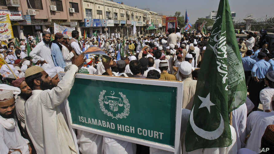 FILE - Men are seen outside the Islamabad High Court, Oct. 11, 2011, in Islamabad, Pakistan. The court this week temporarily barred the extradition to Talha Haroon, 19, wanted by American authorities in connecetion with allegedly hatching a terror pl