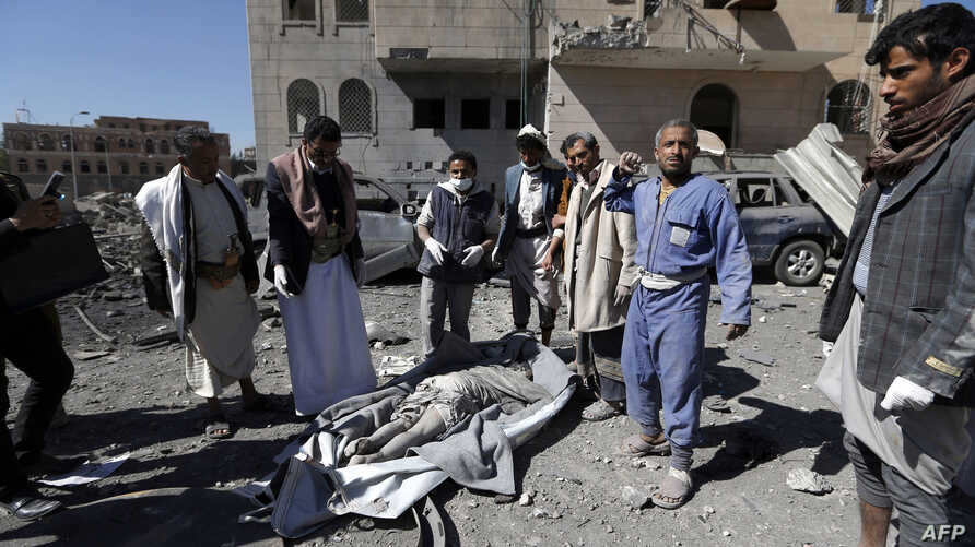 Yemeni Huthis gather around the body of a man killed by air strikes at a detention centre in the capital Sanaa on Dec. 13, 2017.