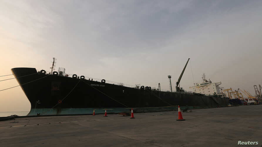 FILE - A cargo ship unloads a shipment of fuel at the Hodeida port, Yemen, May 27, 2018.