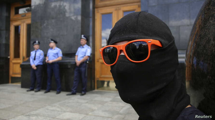An activist takes part in a protest calling for an end to the ceasefire against separatist rebels outside the Presidential Administration Building in Kyiv, June 28, 2014.