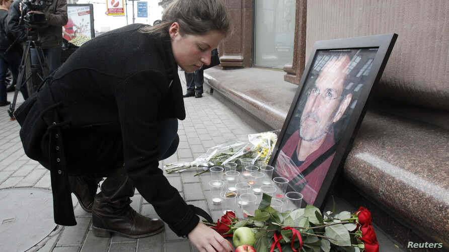 A woman places an apple next to a portrait of Apple founder and former CEO Steve Jobs, outside an Apple store in central Moscow, Oct. 6, 2011. Jobs died at the age of 56 after a long battle with pancreatic cancer.