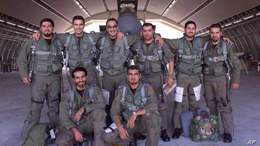 Saudi pilots pose for a group portrait after taking part in U.S.-led coalition airstrikes on Islamic State militants and other targets in Syria, Sept. 24, 2014.