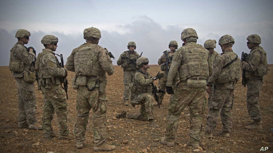 FILE - U.S. Army, U.S. soldiers gather for a brief during a combined joint patrol rehearsal in Manbij, Syria.