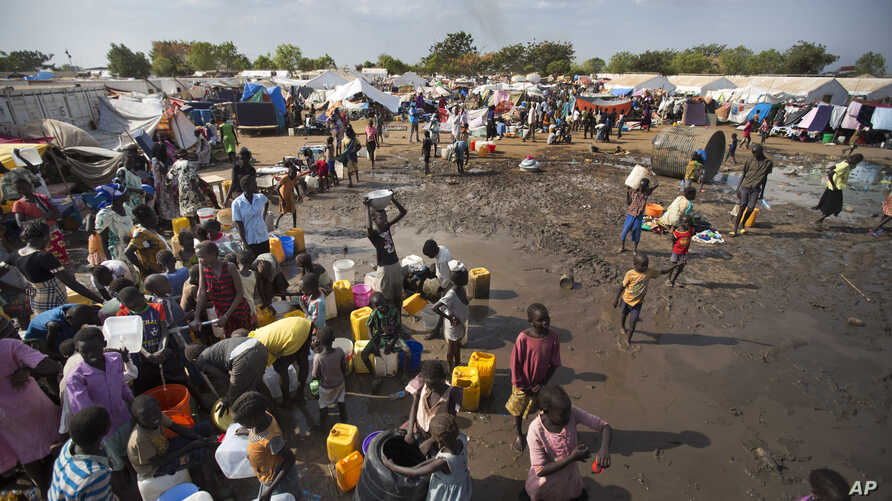 FILE - Displaced people gather around a water truck to fill containers at a United Nations compound that has become home to thousands of people displaced by the recent fighting, in the capital Juba, South Sudan.