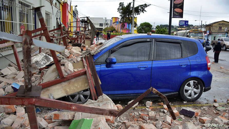 A car covered by debris is seen near a collapsed wall following an earthquake in Quetzaltenango, Guatemala, June 14, 2017.
