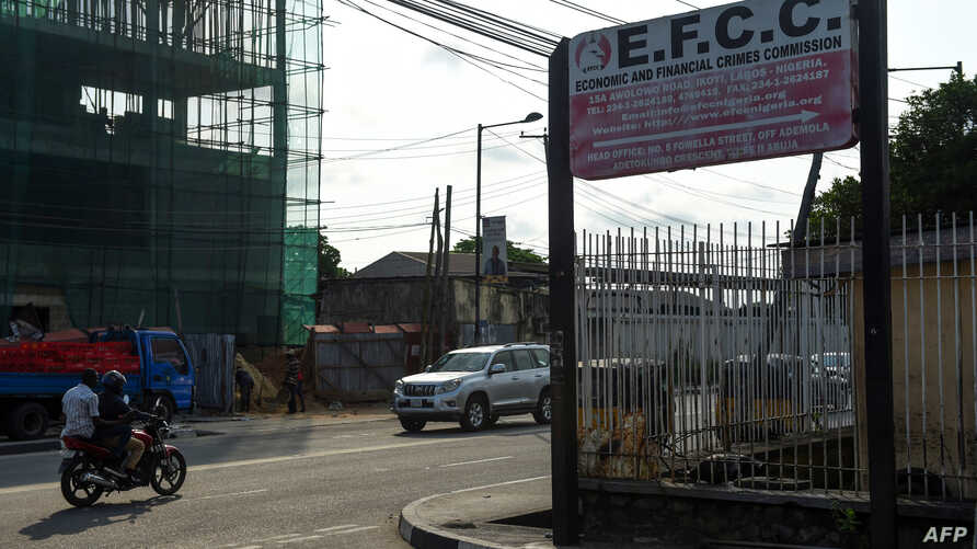 FILE - A motorcycle taxi drives past the sign of the Economic and Financial Crimes Commission (EFCC) in Lagos, Nigeria, Oct. 3, 2016.