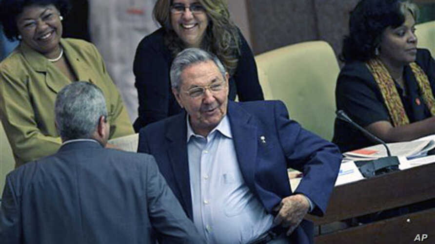 Cuba's President Raul Castro (C) smiles as he talks to parliament members during a parliamentary meeting when it was announced Cuba's supreme governing body has granted a pardon to 2,900 prisoners, in Havana, Cuba, Dec. 23, 2011.