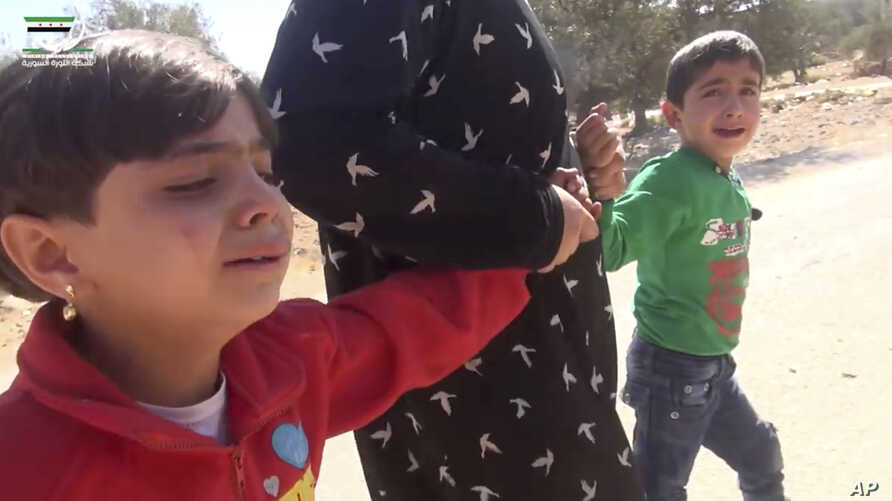 This frame grab from video provided by Muaz al-Shami, Syrian Revolution Network, an opposition activist media organization, that is consistent with independent AP reporting, shows children pulled by an adult after airstrikes killed nearly 30 people,