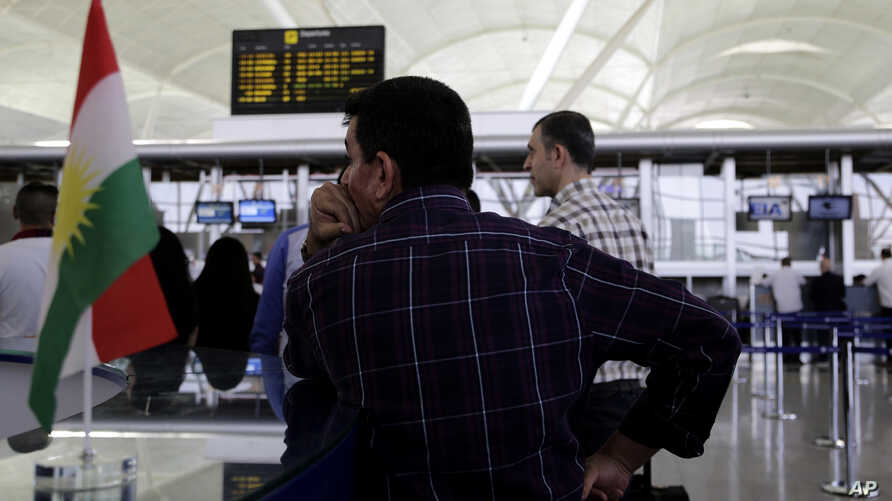 Hours ahead of a flight ban threatened by the central government, passengers file through Irbil international airport Friday, September 29, 2017.