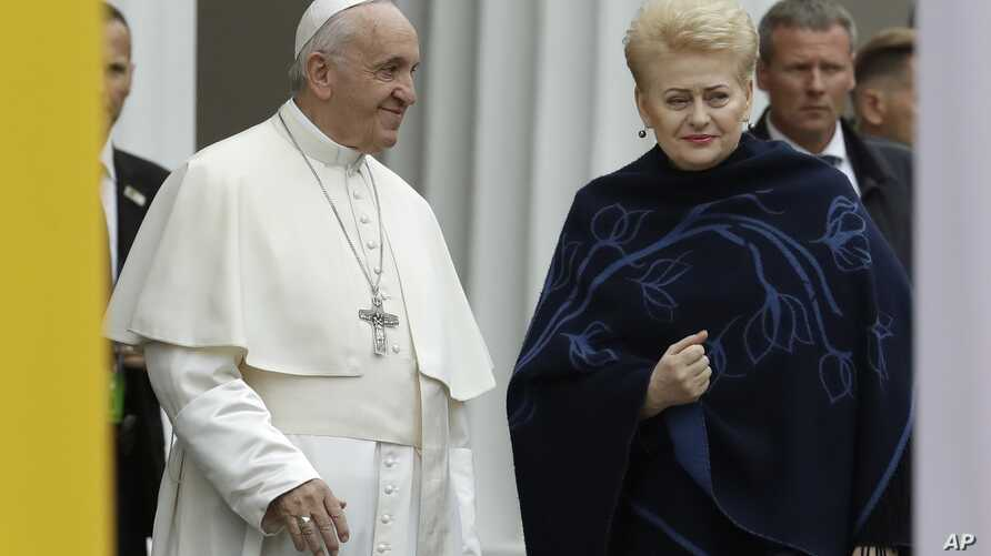 Pope Francis smiles as he arrives with Lithuanian President Dalia Grybauskaite, right, ahead of a meeting with officials, civil society and diplomatic corps in the square in front of the Presidential Palace, in Vilnius, Lithuania, Sept. 22, 2018.