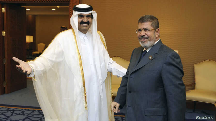 Qatar's Emir Sheikh Hamad bin Khalifa al-Thani (R) greets Egypt's President Mohamed Mursi during the Arab League summit in Doha March 26, 2013.