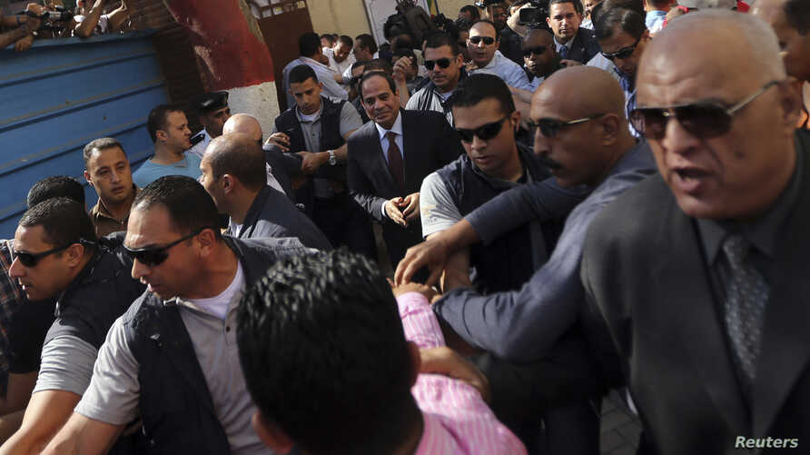 Presidential candidate and former army chief Abdel Fattah al-Sissi arrives with his bodyguards at a polling station in Cairo, May 26, 2014.