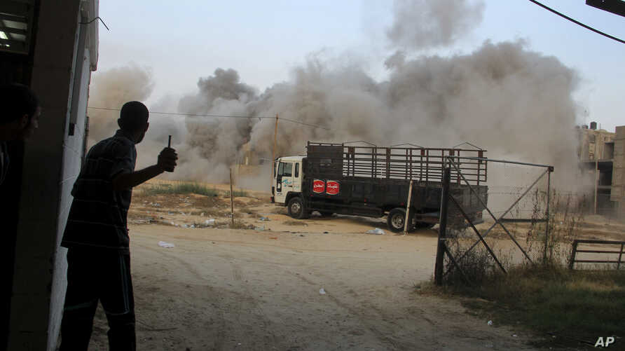 Palestinians take cover during an Israeli air strike on a house in Rafah, in the southern Gaza Strip, July 23, 2014.