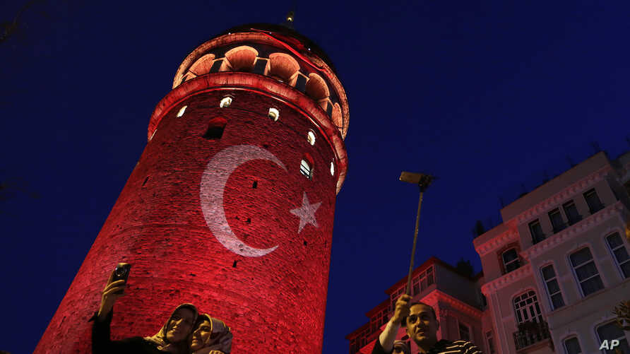 People take photos at the iconic Galata Tower, illuminated in Turkish flag colors, in Istanbul, July 30, 2016. Dozens of staff at Turkey's highest court have been suspended from their jobs as part of the crackdown in the wake of a failed military cou