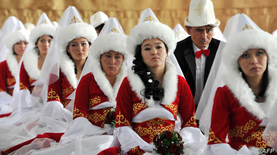 FILE - Kyrgyz brides and bridegrooms pray in the central mosque during a mass wedding ceremony in the capital Bishkek, Oct. 30, 2013. Fifty couples took part in the mass wedding ceremony sponsored by a state company.