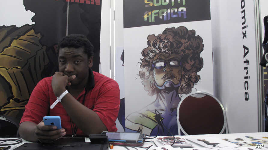 """Bill Masuku, a Zimbabwean comic book artist and writer, sits at a stall at Comic Con Africa, a three-day comic book and pop culture convention in Johannesburg, South Africa, Sept. 15, 2018. The success of Marvel's """"Black Panther"""" film spiked interest"""