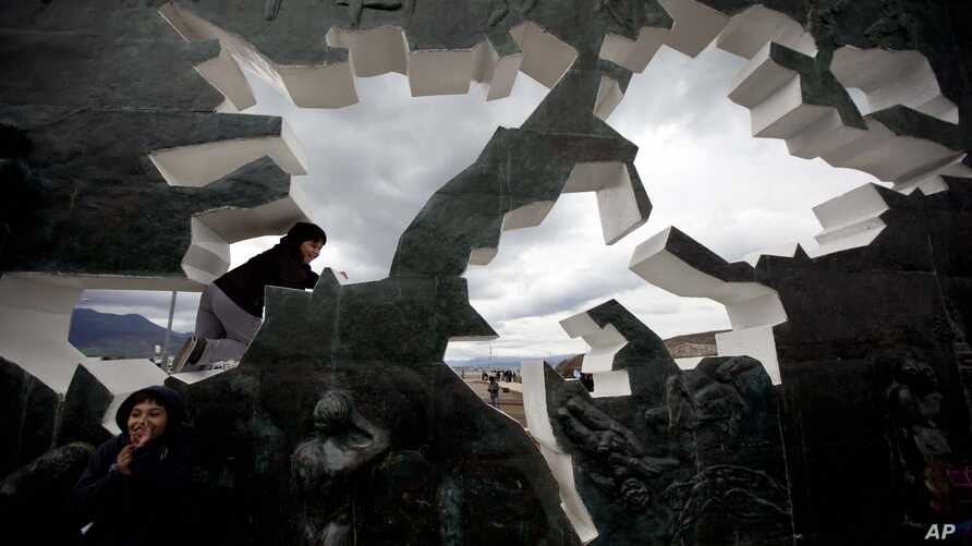 FILE - A child climbs on the Malvinas Island war memorial during a ceremony marking the 30th anniversary of the conflict between Argentina and Great Britain over the remote South Atlantic archipelago, in Ushuaia, Argentina, Monday April 2, 2012.