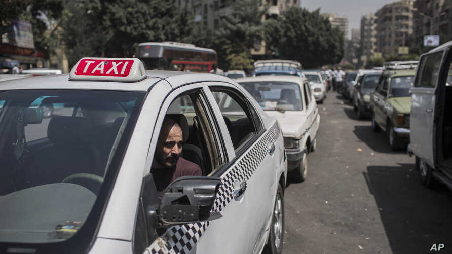 FILE - A taxi driver waits in line for fuel at a gas station in Cairo's neighboring city of Giza, Egypt, Sept. 4 2014. Egypt's parliament approved a law to govern popular ride-hailing apps Uber and Careem, which had faced legal challenges.